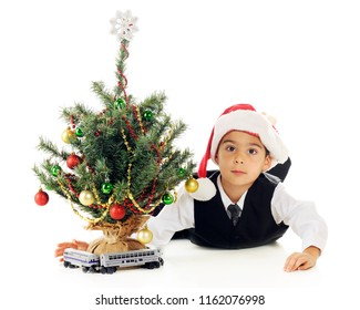 A kindergarten boy playing with his toy train around a tiny decorated Christmas tree.  On a white background.