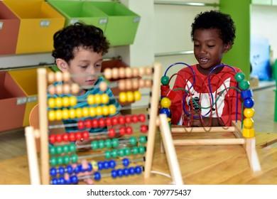 Kindergarten boys having fun learning  equipment  in an international school.teacher ,education, kid and primary school concept .