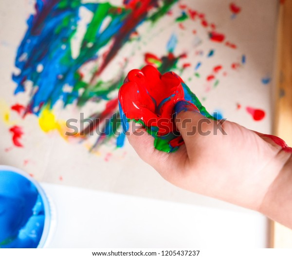 Kindergarten child, playing with paint, creating art