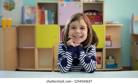 Kindergarten. The child shows different emotions. The girl is 5-6 years old with blond hair. The child is very emotional, shows sadness and joy in the children's playroom. Childhood education concept.