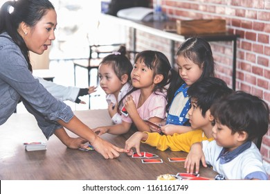 Kindergarten children playing with counting card in class room