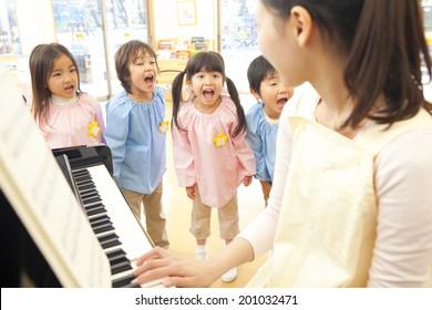Kindergarten children singing along to the piano of kindergarten teachers