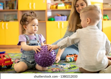 Kindergarten children vie for toy ball. Babies play under the supervision of a caregiver