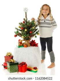 A kindergarten girl standing proudly beside the tiny Christmas tree she's decorated.  On a white background.