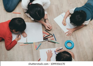 Kindergarten and preschool Kids and teacher drawing,painting on paper learning colorful education top view.