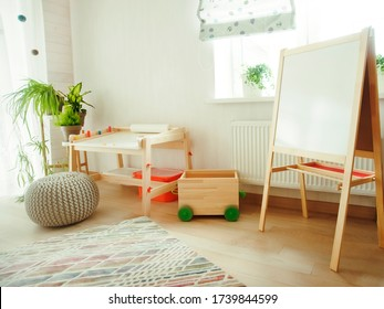 Kindergarten room with easel chair and table for painting. children  space. empty white desk at kindergarten. no people. modern interior. sunlight and plants on windowsill