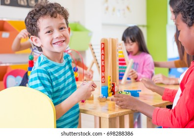 Kindergarten students smile when playing toy in playroom at preschool international,education concept.