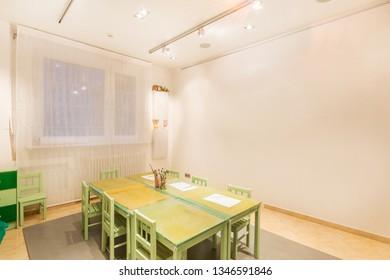Kindergarten tables with painting brush. Preschool class waiting kids.
