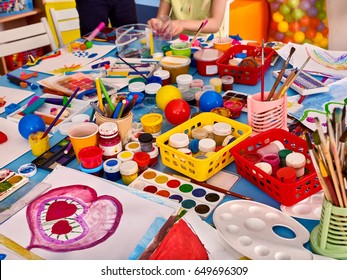 Kindergarten tables with painting brush and teacher in interior . Preschool class waiting kids. Playroom with a lot of object on table. Art room for education children's creativity. Top view.