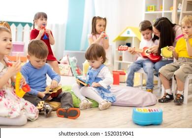 Kindergartenlehrer mit Kindern im Musikunterricht in Tagesbetreuung. Kleine Kleinkinder spielen zusammen mit Spielzeug für die Entwicklung.