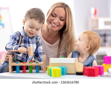 Kindergarten teacher and children playing together in nursery or daycare centre