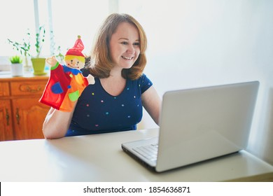 Kindergarten teacher in front of laptop having video conference chat with children. Woman entertaining little kids remotely. Online remote learning and teaching. Homeschooling during quarantine