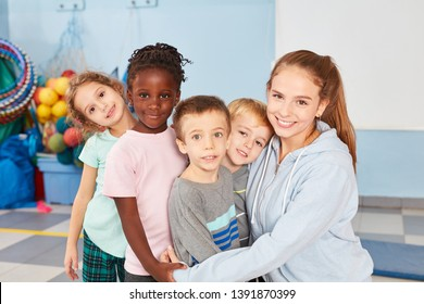 Kindergarten teacher and group of multicultural children as friends hold together
