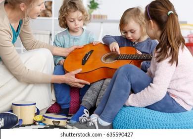 Kindergarten teacher helping little kids to play the guitar