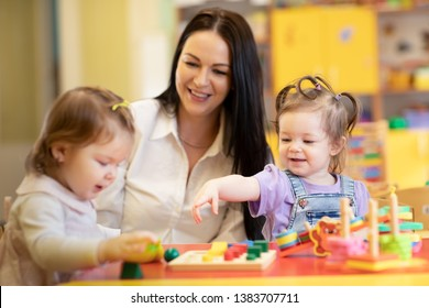 Kindergarten teacher looking after children in day care centre. Nursery babies play together with developmental toys.