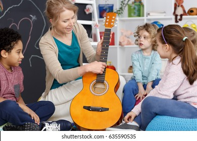 Kindergarten teacher showing kids how to play the guitar