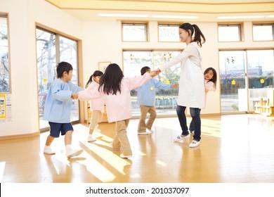 Kindergarteners and kindergarten teachers dancing in a circle