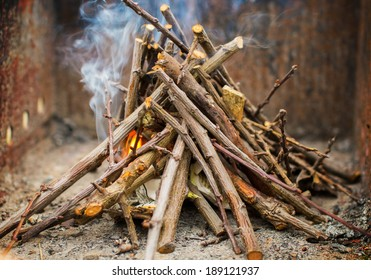 Kindling a fire with small sticks and paper