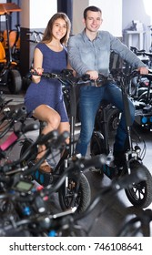 Kindly russian female employee helping adult guy to select bike at rental agency