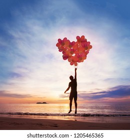 Kindness and love concept, child flying with heart from balloons.