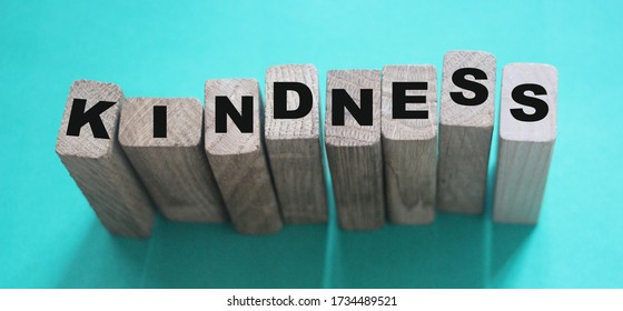 KINDNESS word made with wooden building blocks on neon aquamarine background.