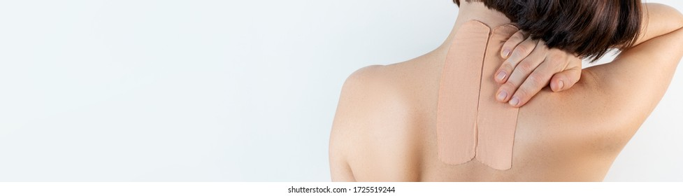 Kinesiology beige taping on the human back on a gray background with a copy space. Dynamic functional bandage taping on the girl's neck. Solution for back and neck pain. Headache.