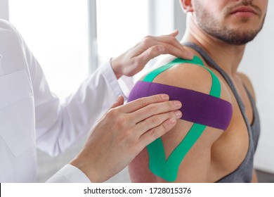 Kinesiology taping. Physical therapist applying kinesiology tape to patient shoulder. Female therapist treating injured shoulder of male athlete. Post traumatic rehabilitation, sport physical therapy.