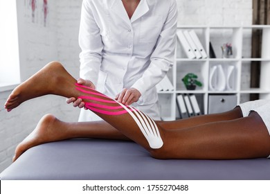 Kinesiology taping. Physiotherapist applying kinesiology tape to patient calf muscle.Therapist treating young female African American athlete. Post traumatic rehabilitation, sport physical therapy.