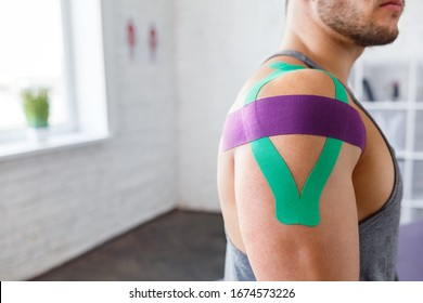 Kinesiology taping. Kinesiology tape on patient shoulder. Injured shoulder treatment of young male athlete. Post traumatic rehabilitation, sport physical therapy, recovery concept.