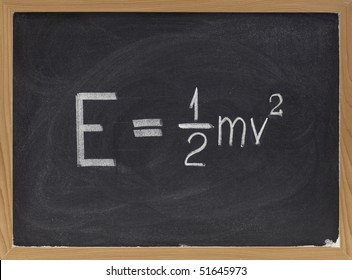 kinetic energy equation of classical Newtonian mechanics connecting it to mass and velocity of a point object  - white chalk handwriting on blackboard