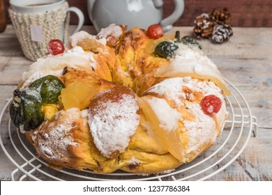 King Cake with nuts - Bolo Rei is a traditional Xmas cake with fruits raisins nut and icing on wooden table.