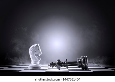 King chess piece defeating by knight chess piece on the chessboard
