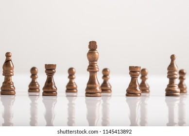 King chess piece with chess figures standing on white table in a conceptual image.