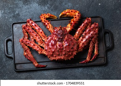 King Crab with lemon and cilantro on black background. Top view.