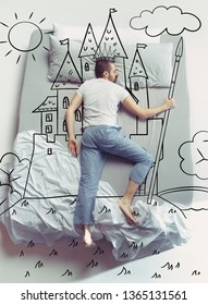 King of the family. Top view photo of young man sleeping in a big white bed at home. Dreams concept. Painted dream about kingdom, castle, crown, sun, landscape, power, control, fairy world, pikestaff.