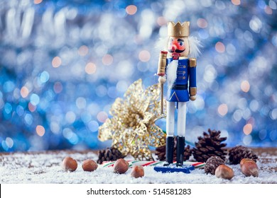 King Nutcracker Statue Standing In Front Of Christmas Background On Snowy Wooden Table. Selective Focus With Copy Space.