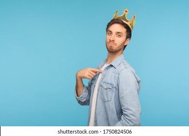 I'm king! Portrait of ambitious man wearing golden crown and pointing himself, looking with arrogance, declaring his authority, superior privileged status. studio shot isolated on blue background