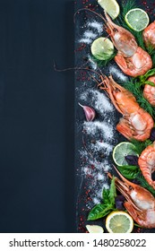 King prawn with spices and herbs: salt, garlic, fennel, basil, lime, pepper, lemon. Royal shrimp on dark background top view, space for text. Mediterranean and seafood concept