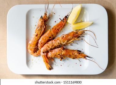 King prawns with lemon. Shrimps on a plate with lemon slices.