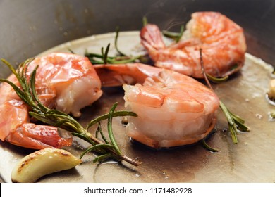 king prawns roasted with rosemary and garlic in an iron pan, food and cokking concept, close up, selected focus, narrow depth of field