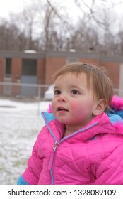 King of Prussia, PA/USA-Jan. 24, 2019:  Tiny two year old toddler girl with bright pink snowsuit, with look of wonder.  Snow scene in the background, side view, waist up.