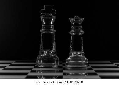King and queen glass chess pieces facing each other in black and white
