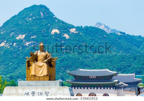 King Sae Jong Dae, engraved under statue in Korean, sitting with Gyeongbokgung Palace gate (Gwanghuamun: written in Chinese), Bugaksan mountain, tourist landmarks at city center, Seoul, South Korea