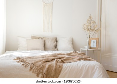 King size bed with white bedding, beige pillows and blanket next to bedside table with flower, coffee bug and print in frame, real photo