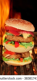 King Size Homemade Cheeseburger On The Hot BBQ Grill With Flame Of Fire On The Black Background, Close Up, Front View