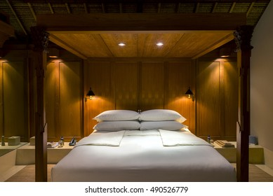 King sized bed timber frame setup with four pillows against wood paneling wall. White linen bedroom set.