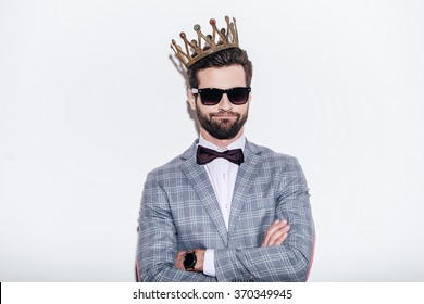 King of style. Sneering young handsome man wearing suit and crown keeping arms crossed and looking at camera while standing against white background