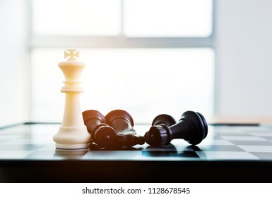 The King winning in battle chess game stand on chessboard.