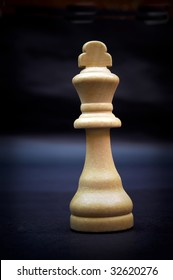 King, wooden chess piece isolated on dark background.
