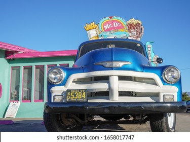 Kingman, Arizona / USA - 21 Oct 2019: Looking up at a blue vintage Chevrolet 3100 farm truck. Behind is a colourful Route 66 diner with pastel pink / green paint, neon burger and root beer sign.